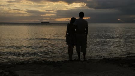 słoneczko : Man and woman are embracing on the beach and watch the sunset silhouette of couple in love hugging at beach.