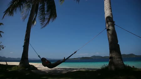 invite : silhouette of man in hammock on the beach.Idyllic beach with coconut trees and hammock.Travel concept
