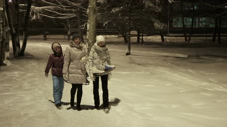 śnieżka : Mother and daughters walking in the winter, night park.