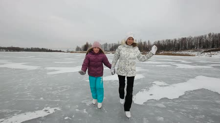 patim : Happy girls  ice skating in natural rink frozen lake.Ice skaters on a frozen Lake.