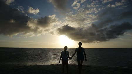 linha do horizonte : Happy young girls holding hands walking on the beach at sunset, silhouettes of people.Travel concept.Family,summer vacation.Happy family