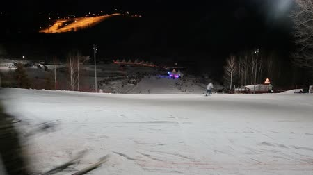 high speed track : Skiers and snowboarders at night.Skiers and snowboarders skiing downhill in the winter season.
