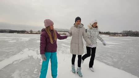 escorregadio : Mother with daughters ice skating in natural rink frozen lake.