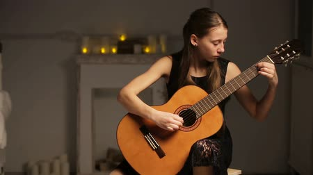 adolescência : Young girl in black dress playing guitar in the dark romantic room.Young girl playing music on acoustic guitar.