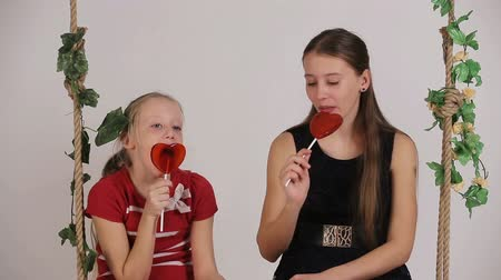 pirulito : Young girls sitting on the swing and enjoy candy.Young girls sit on a swing and eat lollipop. Stock Footage
