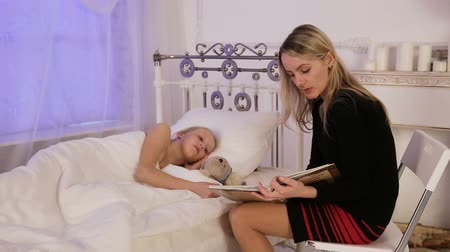identical : Mother reading a book to her daughter in a dark bedroom.Young girl lies in a bed in the bedroom, the mother is sitting across from her and reads her a book.