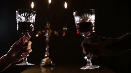 kırmızı şarap : Two glasses of wine clink.Red wine bottle, two wine glasses,burning candles in a chandelier.