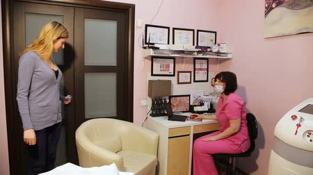 registrace : Young woman on reception at the beautician.Woman patient comes to the doctors office.