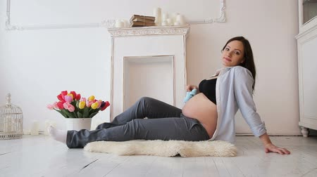 booties : Pregnant woman sitting on the floor in the living room holding baby shoes on her belly.Family concept.Maternity concept. Stock Footage