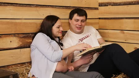 meg nem született : Pregnant woman and her husband sitting on the hay and read a book.Family concept.Maternity concept.