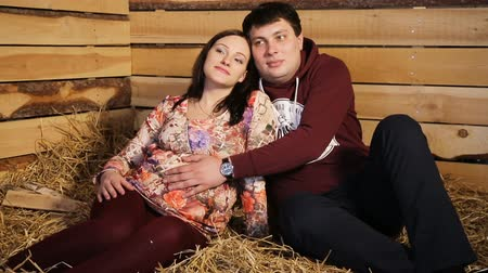 doğmamış : Pregnant woman and her husband sitting on the hay.Family concept.Maternity concept.