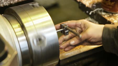 production tool : tapping threads in stainless steel using a hand tap.Turning lathe in action.