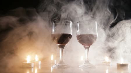 porce : Two glasses of wine on black background and burning candles in the smoke.Red wine glasses.
