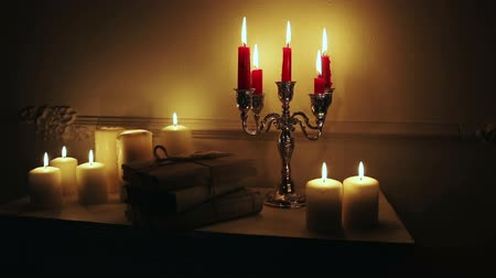 majorság : Retro candlesticks with candles on fireplace, on black background.