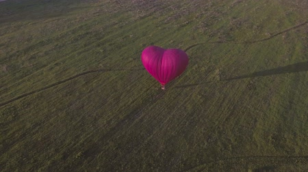 tej : Red balloon in the shape of a heart.Aerial view:Hot air balloon in the sky over a field in the countryside in the beautiful sky and sunset.Aerostat fly in the countryside. Stock mozgókép