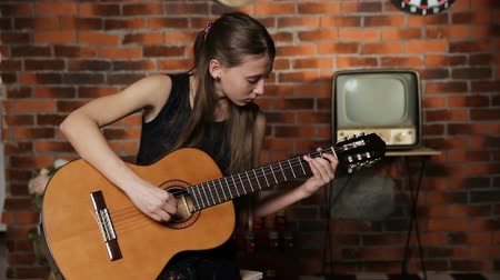 singers : Young girl in black dress playing guitar in the dark romantic room.Young girl playing music on acoustic guitar.