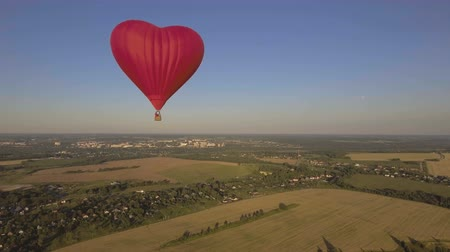 tej : Red balloon in the shape of a wheat heart.Aerial view:Hot air balloon in the sky over a field in the countryside in the beautiful sky and sunset.Aerostat fly in the countryside. 4K video,ultra HD. Stock mozgókép