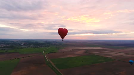 tej : Red balloon in the shape of a heart.Aerial view:Hot air balloon in the sky over a field in the countryside.Aerostat fly in the countryside. Stock mozgókép