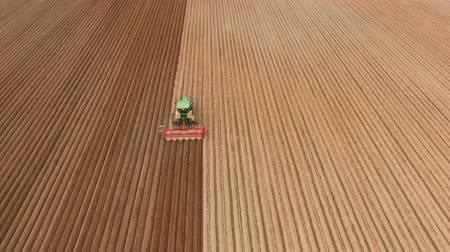 сельскохозяйственный : Aerial view of ploughed field with tractor sowing seeds of wheat.