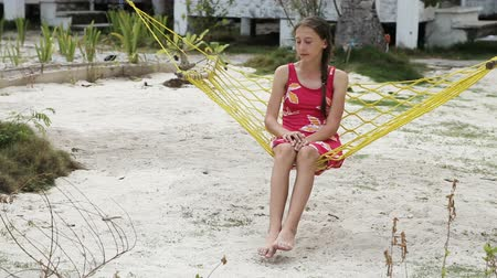 novela : young girl sitting and swinging in a hammock on the beach under palm trees.