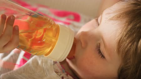 nipple : The young girl lies on a bed and drinking from a bottle for feeding the juice.