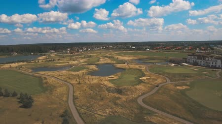 kurzus : Aerial view of golf green and protective sand trap.Golf course on the background of blue sky and clouds.