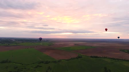 tej : Hot air balloons in the sky over a field in the countryside.Aerial view:Hot air balloons in the sky over a field in the countryside in the beautiful sky and sunset.Aerostat fly in the countryside.