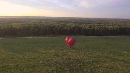 uçan : Red balloon in the shape of a heart.Aerial view:Hot air balloon in the sky over a field in the countryside in the beautiful sky and sunset.Aerostat fly in the countryside. Stok Video