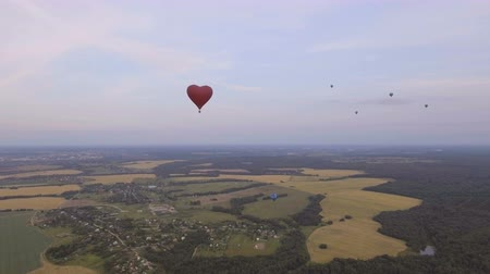 tej : Red balloon in the shape of a heart.Aerial view:Hot air balloon in the sky over a field in the countryside in the beautiful sky and sunset.Aerostat fly in the countryside. 4K video,ultra HD.
