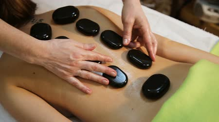 kamień : Beautiful woman relaxing in spa salon with hot stones on body. Beauty treatment therapy.young woman receiving hot stone massage.Stone therapy,stone massage.Spa treatments, beauty center. In a the beauty salon.