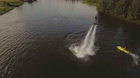 propulsion : Young girl on the Hover board on the river, water jet spray.Young girl on the flying board flies over the lake water.Teen on wake-board.Aerial:Fly board rider.Aerial video.4K video.