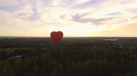 dirigível : Red balloon in the shape of a heart.Aerial view:Hot air balloon in the sky over a field in the countryside in the beautiful sky and sunset.Aerostat fly in the countryside. 4K video,ultra HD.