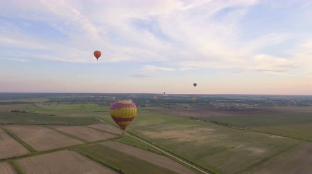 tej : Hot air balloons in the sky over a field in the countryside.Aerial view:Hot air balloons in the sky over a field in the countryside in the beautiful sky and sunset.Aerostat fly in the countryside. 4K video,ultra HD.