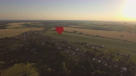 tej : Red balloon shape of a wheat heart.Aerial view:Hot air balloon in the sky over a field in the countryside in the beautiful sky and sunset.Aerostat fly countryside. 4K video,ultra HD. Stock mozgókép