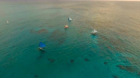 filipíny : Aerial view: Sunset over the sea in the background boats,sailing boat, orange sky and islands.Tropical beach at sunset. Sailing boats at sunset in the sea. White sand beach. Travel concept. Beautiful serene scene. Philippines, Boracay. 4K video. Travel co