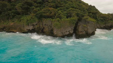 bakış : Rocky shore on the tropical sea with the rainy cloud. Aerial view:Stormy weather on island.Rocks in sea in cloudy gloomy weather. Big waves crushing on the shore of a tropical island with palm trees during a storm.Philippines, Boracay. 4K video. Travel co Stok Video