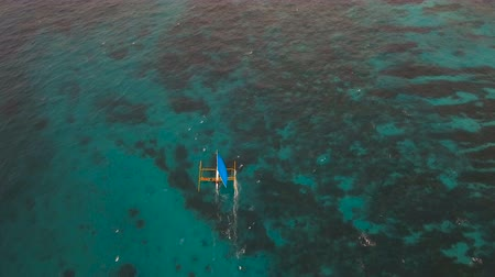 törekvés : Sailing boat in blue, turquoise lagoon. Sailing ship yachts with blue sails in the ocean.Aerial view:Sail boat on sea. Sailing ship yachts in the sea.Aerial video. Philippines, Boracay. 4K video. Travel concept. Aerial footage. Stock mozgókép