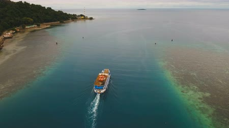 mindanao : Aerial view passenger ferry floats in the blue sea.Asian passenger boat floating in the ocean.Philippines, Camiguin. Passenger ferry boat Camiguin to Mindanao. 4K video.Travel concept. Aerial footage.