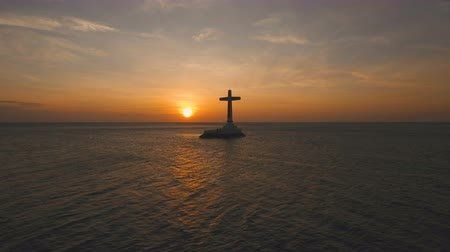 daan : Aerial view Sunken Cemetery cross at sunset in Camiguin Island, Philippines. Large crucafix marking the underwater sunken cemetary of the coast of camiguin island near mindanao in the Philippines. Catholic cross in the water on the background of sky and c