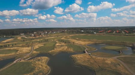 kurzus : Aerial view of golf green and protective sand trap.Golf course on the background of blue sky and clouds.Aerial view of a beautiful green golf course.4K video. Stock mozgókép