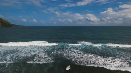 prancha de surfe : Aerial view from drone of a swimming group with surfers in open sea with beautiful swell waves. Education surfers in the ocean with big waves. Active sport leisure in Pacific Ocean.Philippines, Puraran,Catanduanes. 4K video. Travel concept. Aerial footage
