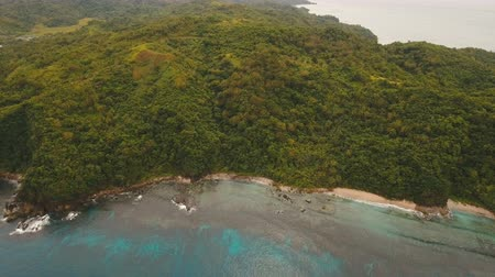 высота над уровнем моря : Wild beautiful beach with coconut palms. Aerial view: sea and the tropical island with rocks, beach and waves. The coast of the tropical island with the mountains and the rainforest on a background of ocean with big waves.. Seascape: rocks, ocean. 4K vide