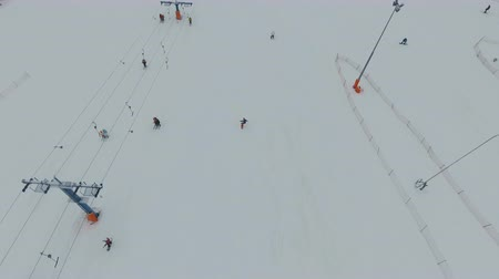 вниз : Aerial view: Skiers and snowboarders going down the slope in winter day. Skiers and snowboarders enjoying on slopes of ski resort in winter season. 4K video, aerial footage.