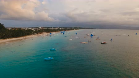 sail rock : Aerial view: Sunset over the sea in the background boats,sailing boat, orange sky and islands.Tropical beach at sunset. Sailing boats at sunset in the sea. White sand beach. Travel concept. Beautiful serene scene. Philippines, Boracay. 4K video. Travel co