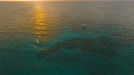 přešel : Aerial view: Sunset over the sea in the background boats,sailing boat, orange sky and islands.Tropical beach at sunset. Sailing boats at sunset in the sea. White sand beach. Travel concept. Beautiful serene scene. Philippines, Boracay. 4K video. Travel co