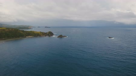 высота над уровнем моря : The coast of the tropical island with the mountains and the rainforest on a background of ocean with big waves.Aerial view: sea and the tropical island with rocks, beach and waves. Seascape: sky, clouds, rocks, ocean. 4K video. Philippines, Catanduanes. 4