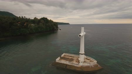 daan : Aerial view Sunken Cemetery cross in Camiguin Island, Philippines. Large crucafix marking the underwater sunken cemetary of the coast of camiguin island near mindanao in the Philippines. Catholic cross in the water on the background of sky and clouds .. T Stock Footage