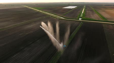 irrigate : Irrigation equipment watering freshly seeded field.Irrigation of farmland to ensure the quality of the crop.Aerial view: irrigation system watering a farm field.