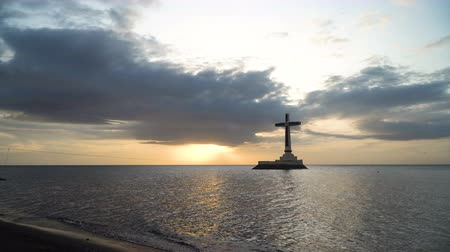daan : Sunken Cemetery cross in Camiguin Island, Philippines. Large crucafix marking the underwater sunken cemetary of the coast of camiguin island near mindanao in the Philippines. Catholic cross in the water on the background of sky and clouds .. The Sunken Ce