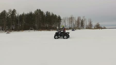 quadbike : ATV race on the snow. Rider driving in the quadbike race. Man riding ATV in sand in protective clothing and a helmet. Racer rides a quad motorbike in the cross racing. Quadrocycle on the snow cover. 4K video